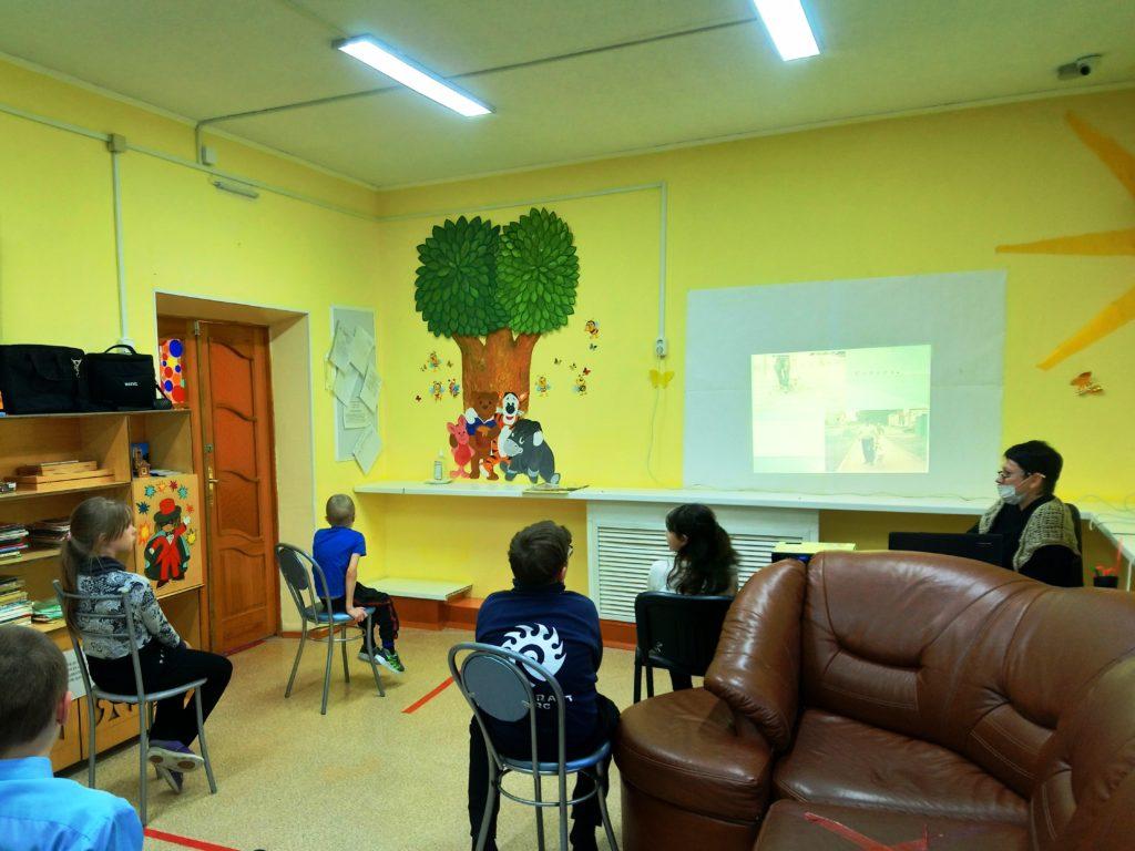 В помещении, дети сидят на стульях, смотрят презентацию. Специалист сидит справа от детей.