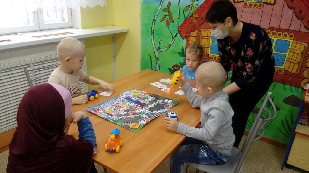 Дети сидят за столом, специалист стоит возле стола