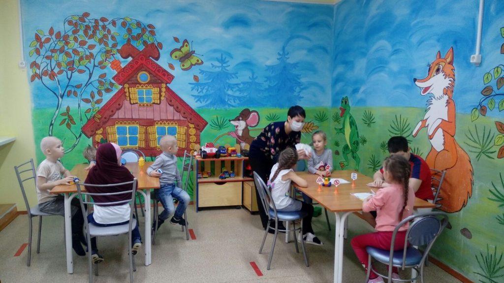 Дети сидят за столами, специалист стоит возле стола
