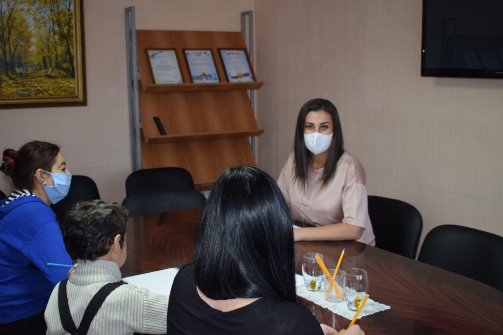 За столом сидят психолог отделения социального сопровождения граждан, семья (две женщины, ребенок).