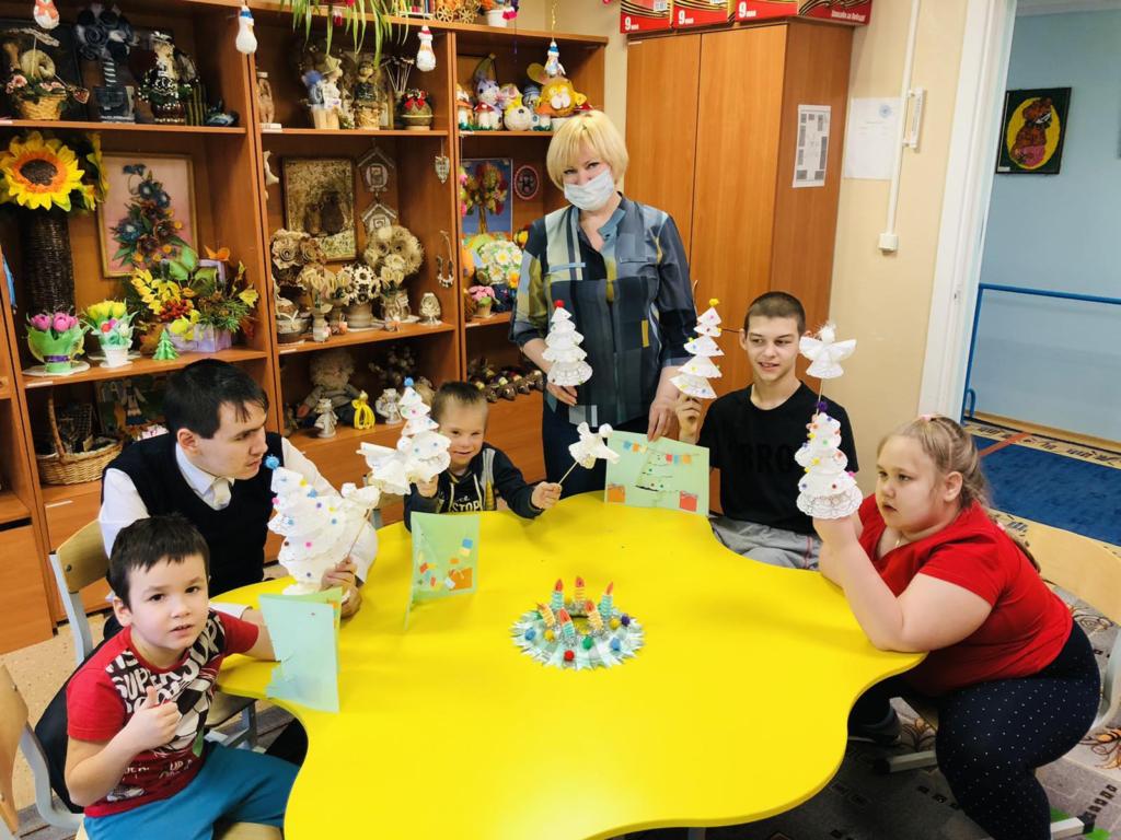 На фотографии дети за столом, в руках у них поделки, рядом стоит инструктор по труду.