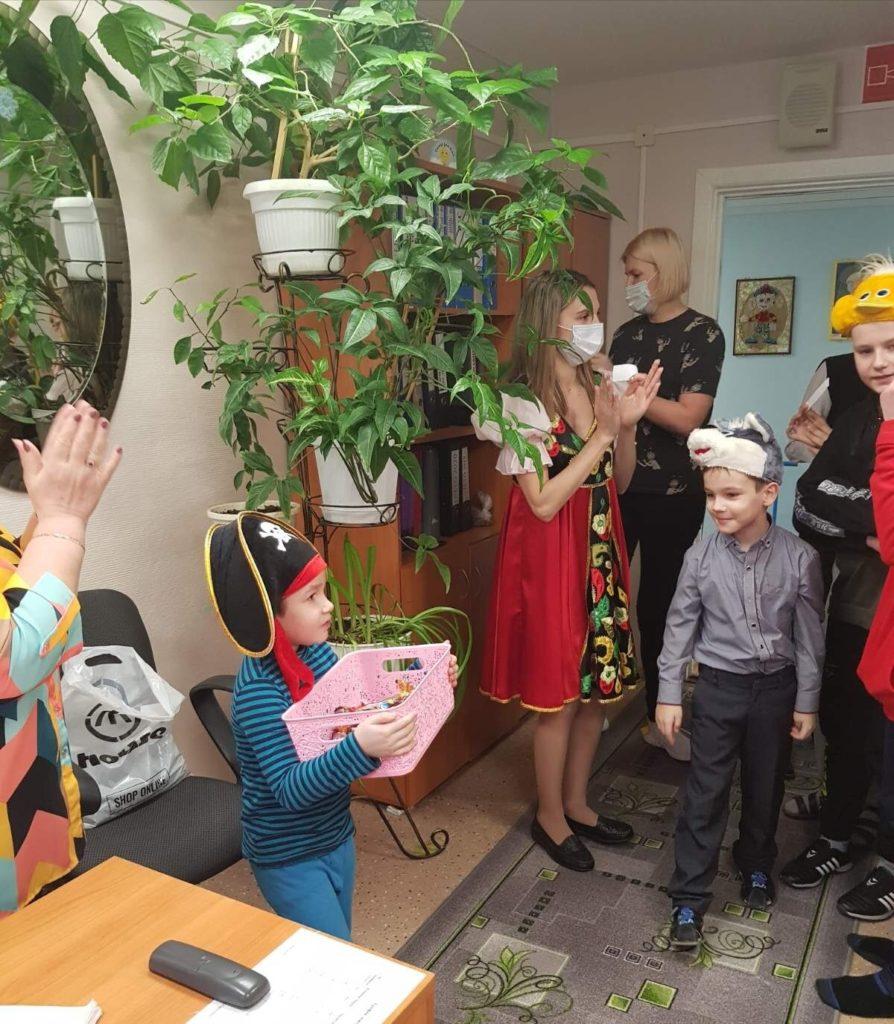 Фотография: ребенок с коробкой конфет в руках, рядом специалисты отделения и мальчики.