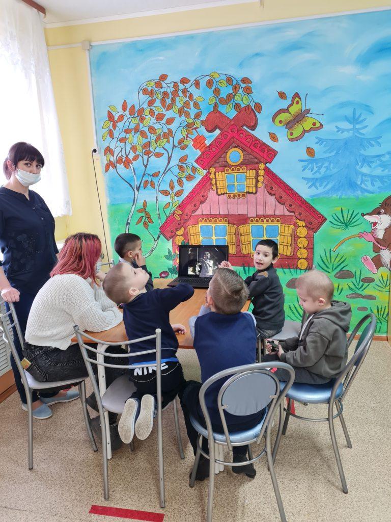 Фотография: дети сидят за столом, смотрят презентацию.