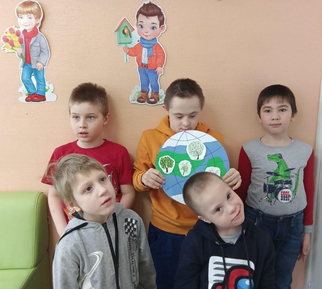 На фотографии стоят мальчики, в центре мальчик держит в руках макет Земли.