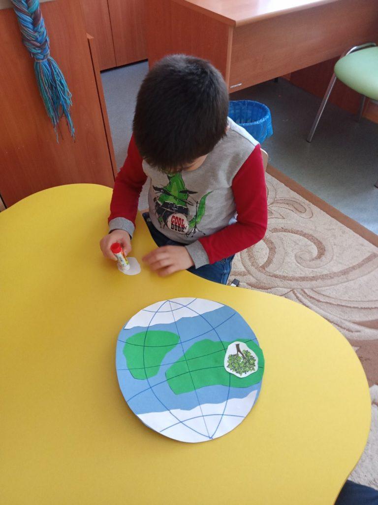 На фотографии мальчик сидит за столом, в руках клей. Делает макет Земли.