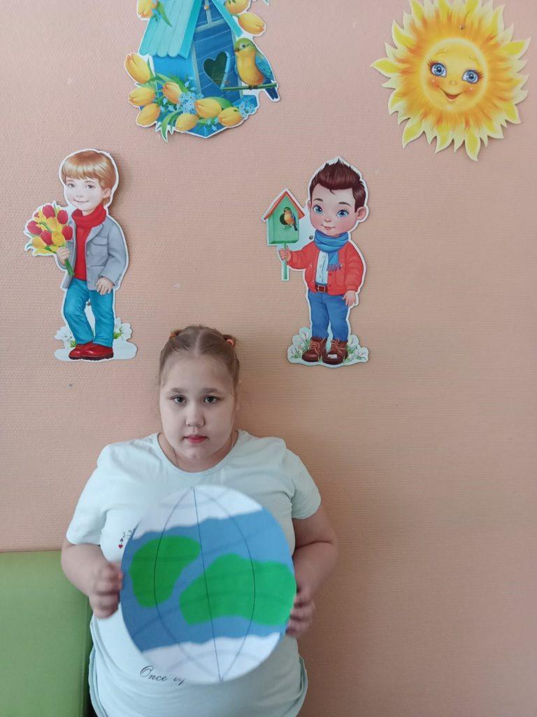 На фотографии стоит девочка , в руках держит макет Земли.